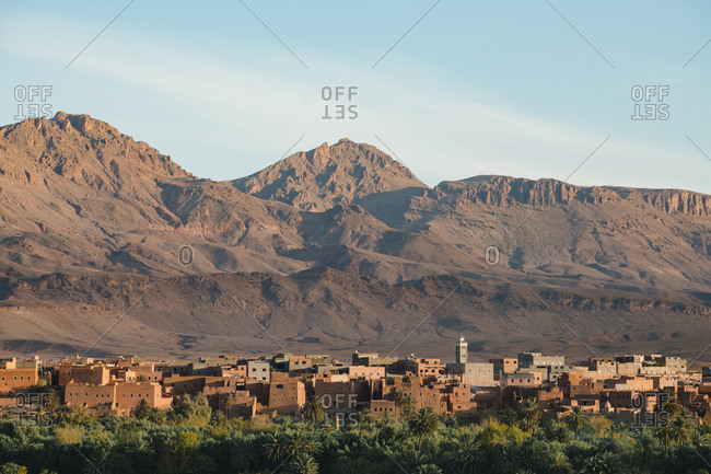 High angle view of houses in village by Atlas Mountains against sky