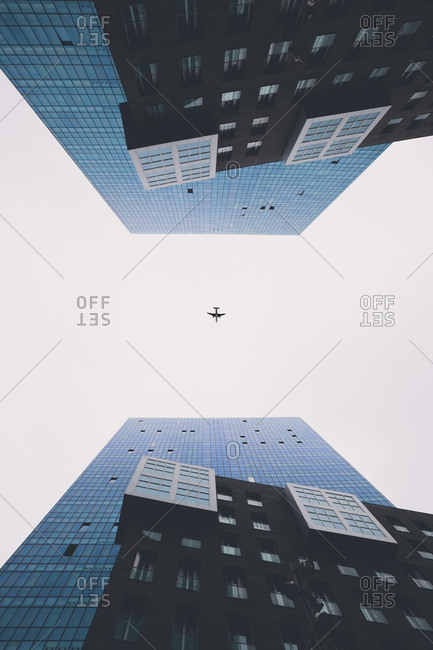 Directly below shot of airplane flying in clear sky seen amidst modern buildings in city