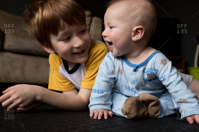 Boy sitting on floor by happy baby brother