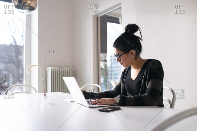 Young creative woman working alone on laptop in conference room