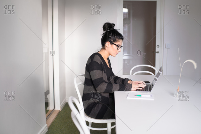 Young creative woman working on laptop in conference room