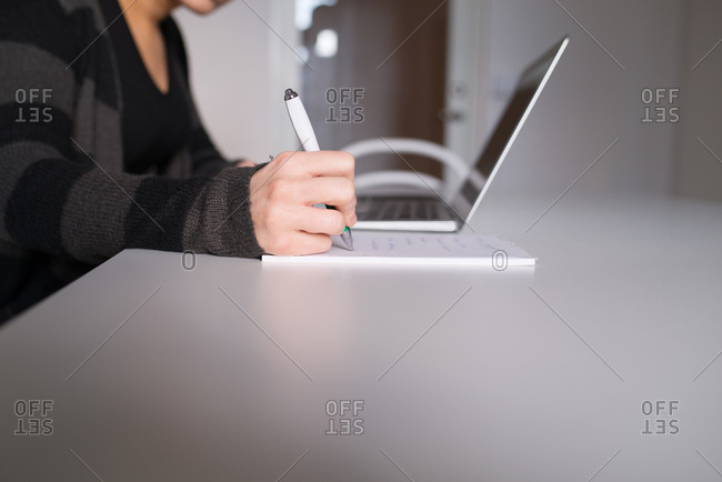 Close up of young woman's hand writing notes on note pad