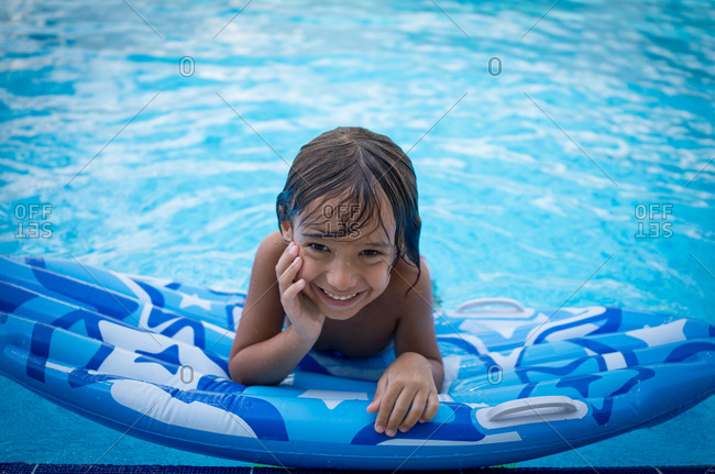 Happy young boy on flotation device at edge of pool