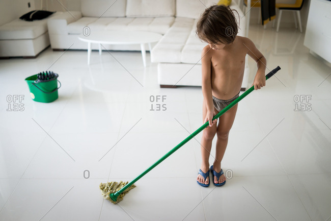 Young boy helping mop floor