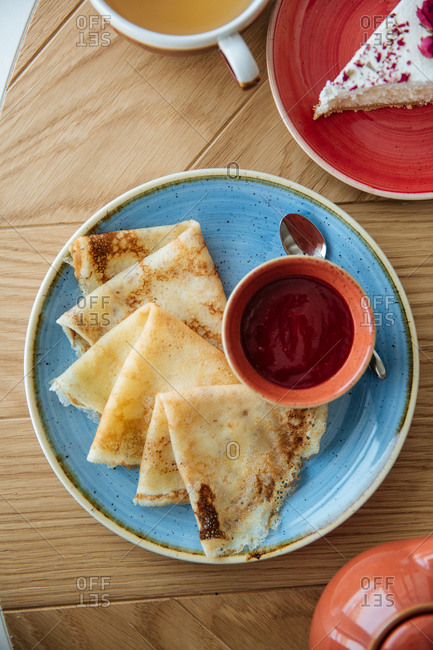 Crepes with a side of fruit sauce served on a wooden table