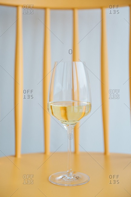 Glass of white wine on a yellow chair