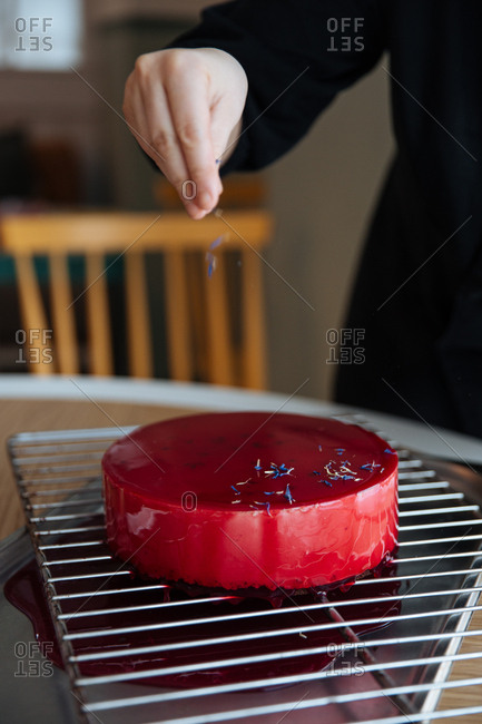 Person topping a cake with sprinkles
