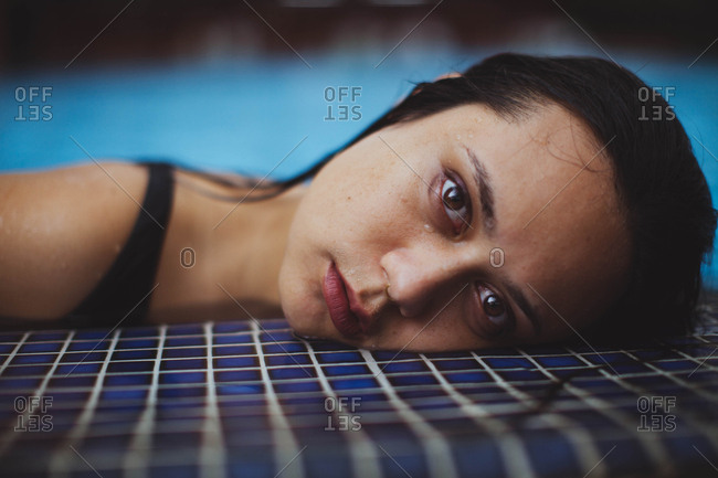 Portrait of dark haired woman with nose ring in a swimming pool