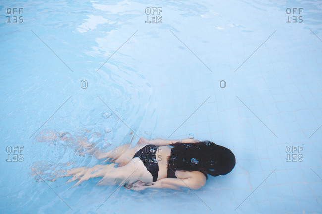 Dark haired woman in black bikini swimming underwater