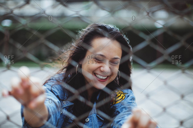 Portrait of dark haired woman behind a chain link fence