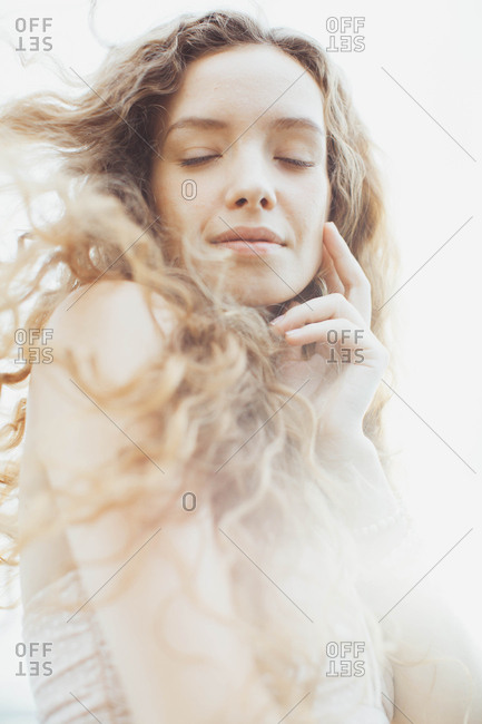 Portrait of a beautiful young woman with long curly blond hair blowing in the wind