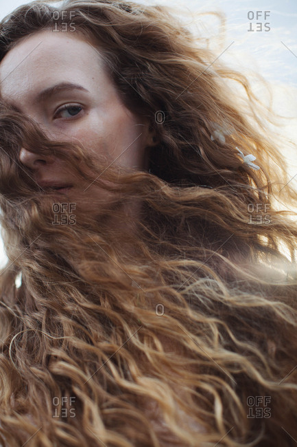Portrait of a woman with long curly blond hair blowing in the wind