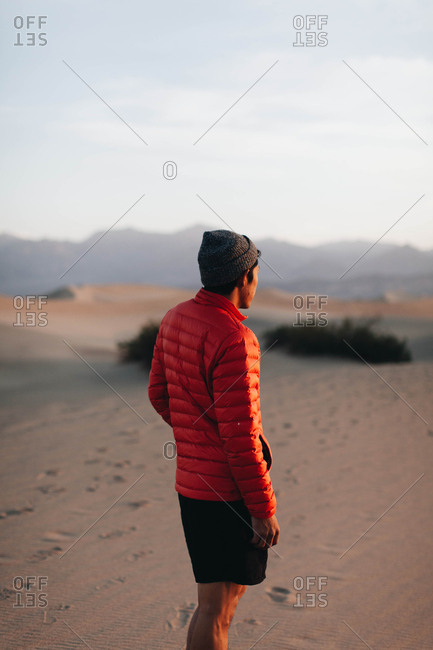 Man looking out over sand dunes during sunrise in Death Valley