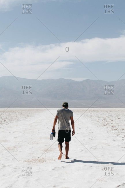 Man walking barefoot over the salt flats of Badwater Basin in Death Valley