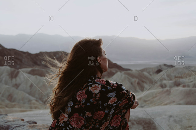 Carefree woman looking out over rock formations of Zabriskie Point in Death Valley