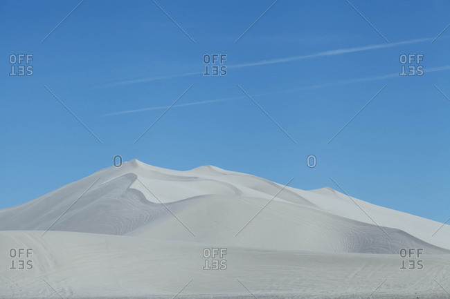 White sand dunes in front of a clear blue sky