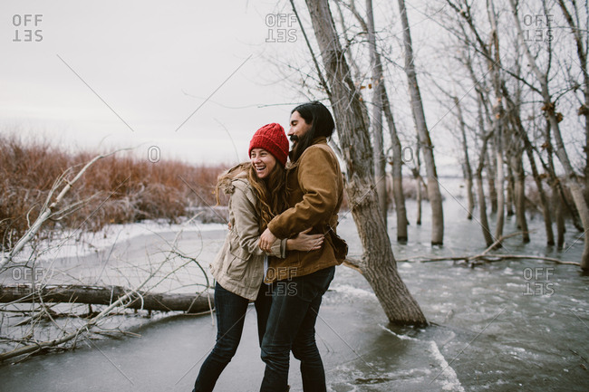 Couple hugging and laughing on a frozen lake