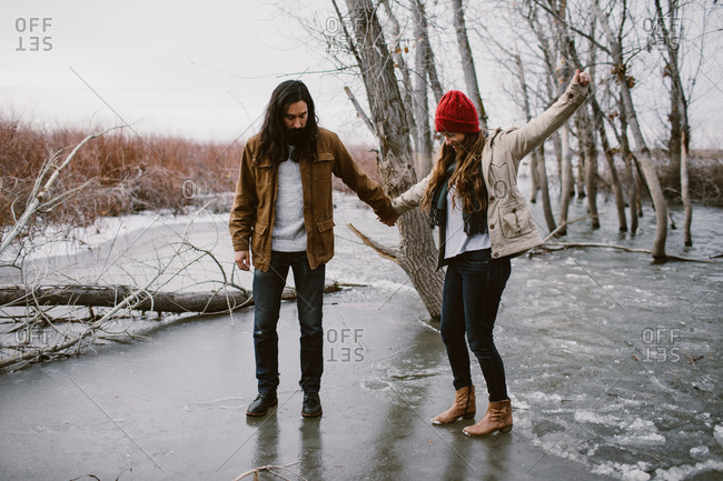Couple playing on a frozen lake during winter