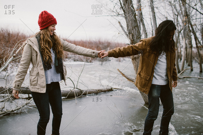 Couple skating and holding hands on a frozen lake outdoors