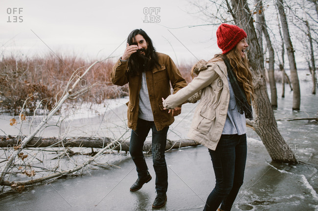 Couple playing and laughing on a frozen lake