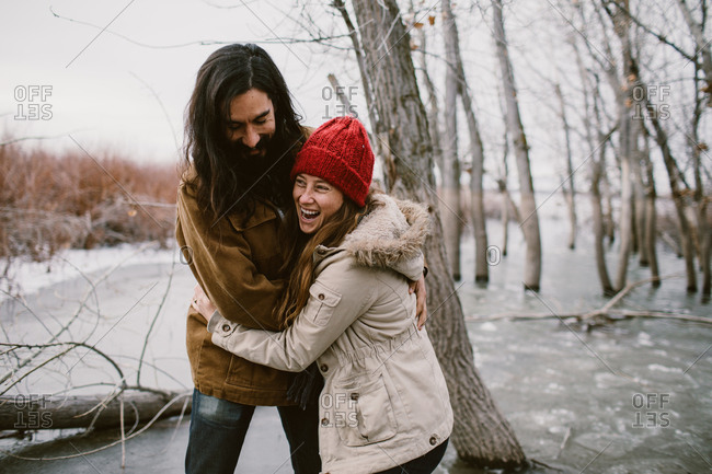Man and woman hugging and laughing on a frozen lake outdoors