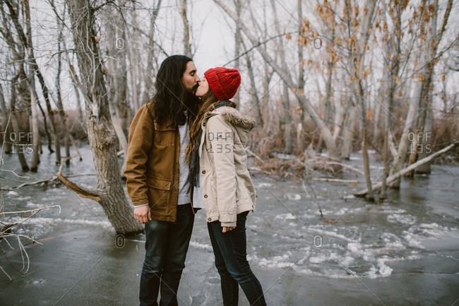 Man and woman kissing on a frozen lake outdoors