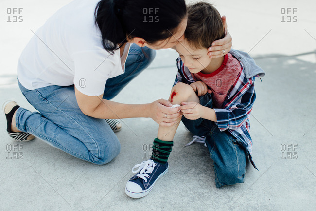 Mother nurses a bleeding knee of her son after an accident in a playground