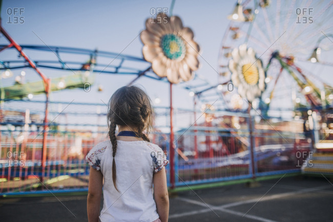 Oregon, USA - July 21, 2017: Rear view of girl with pigtails looking at amusement park rides