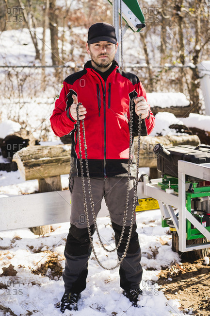 Portrait of worker holding chains while standing on snow covered field in backyard