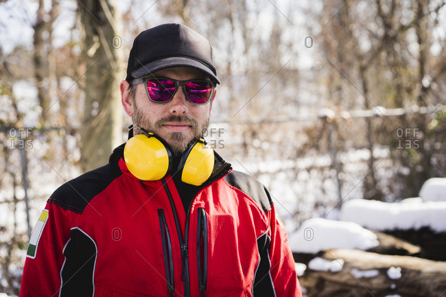 Portrait of carpenter wearing protective workwear standing in backyard during winter
