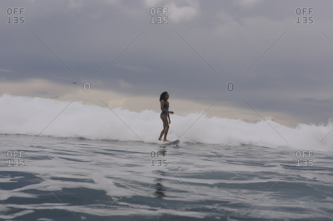 Side view of woman surfing on sea against cloudy sky