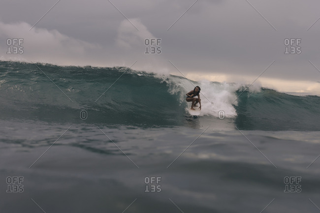 Woman surfing on sea against cloudscape