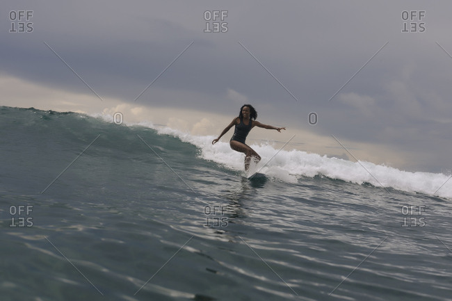 Woman surfing on sea against cloudy sky