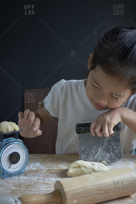 Girl measuring dough on scale in kitchen