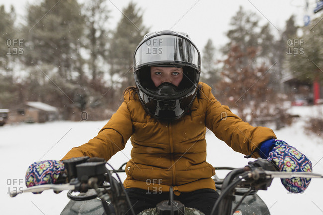Portrait of girl snowmobiling on snow covered field in forest