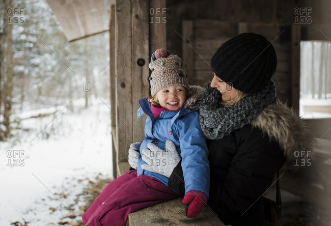 Happy mother standing by daughter sitting on window during winter