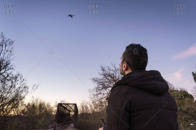 Man flying drone against sky during sunset