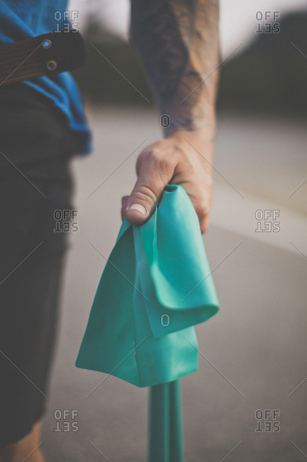 Midsection of man holding fabric while standing on road at park
