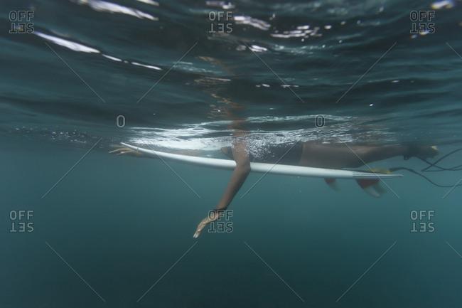 Side view of woman surfing undersea