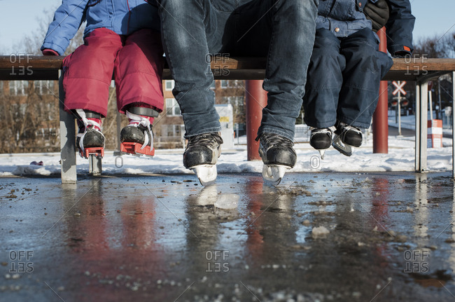 Low section of father and children wearing ice skates sitting on table at ice rink