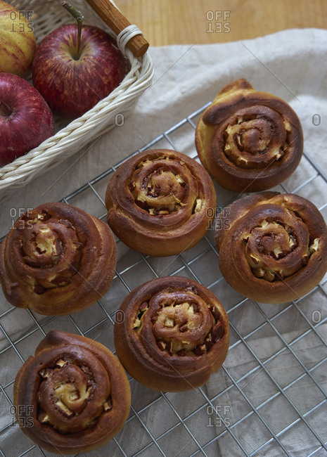High angle view of baked cinnamon buns on metal grate at kitchen