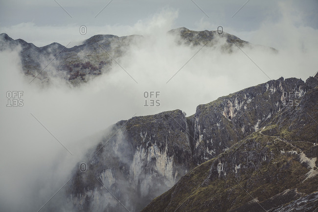 Idyllic view of mountains amidst clouds