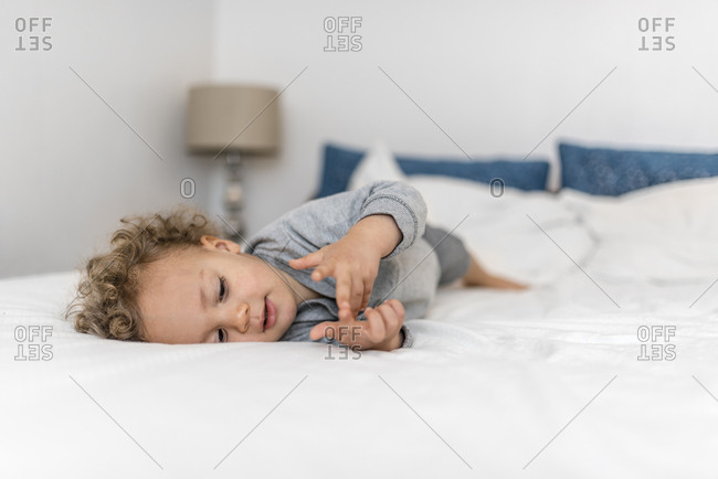 Boy laying in bed counts on his fingers