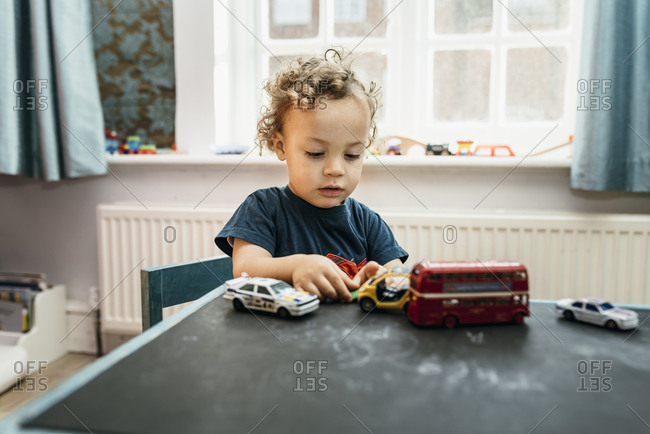 Boy plays with car toys at desk