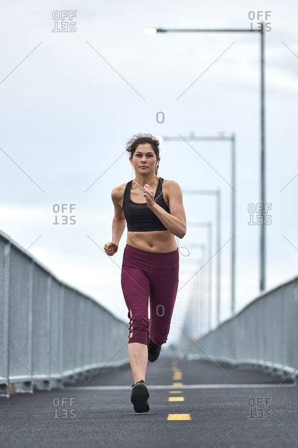 Confident woman running while training on bridge, Montreal, Quebec, Canada