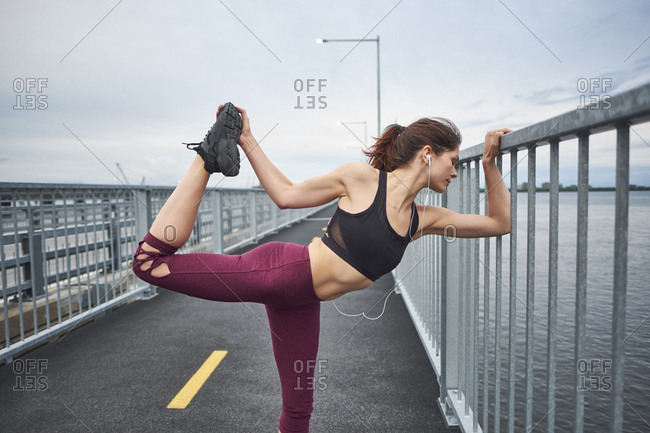 Confident woman warming up for training on bridge, Montreal, Quebec, Canada