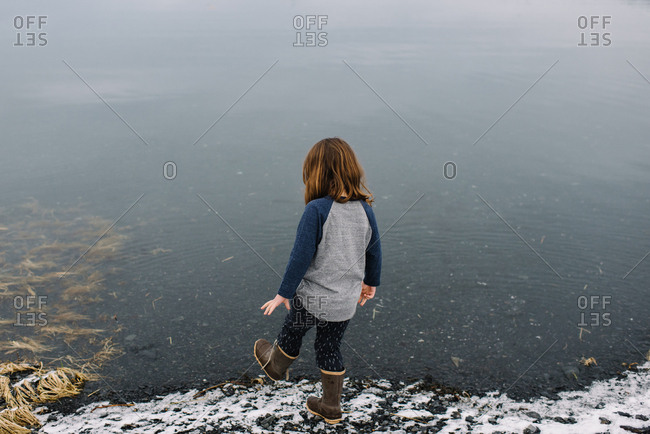 Rear view of girl standing on lakeshore in winter