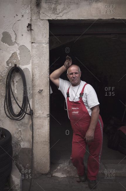 Modica, Sicily, Italy - July 15, 2014: Portrait of an Italian mechanic standing in his garage
