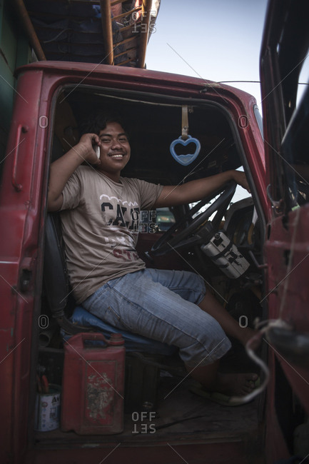 Makassar, Sulawesi, Indonesia - September 2, 2013: Portrait of a trucker sitting in driver seat using cell phone