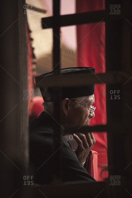 Rantepao, Sulawesi, Indonesia - September 3, 2013: Profile view of man sitting at a Toraja funeral